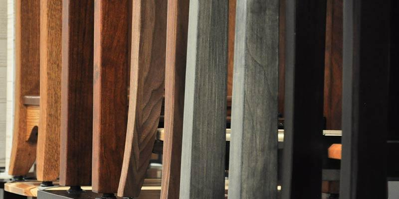 Row of different styles of chair legs in a variety of colors and finishes